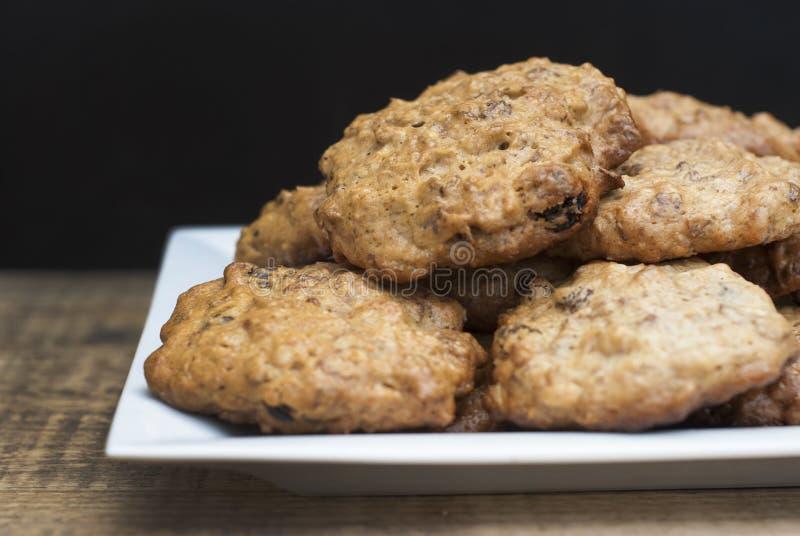 Biscuits de farine d'avoine faits maison dans le plat de place blanche, sur le conseil en bois et le fond noir Casse-croûte doux  photos stock