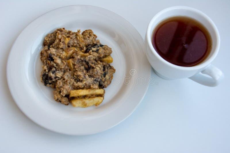 Biscuits de farine d'avoine faits maison de plat avec le chapeau du thé sur le fond blanc image stock