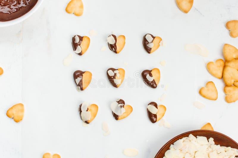 Biscuits de forme de coeur couverts du chocolat et d'amandes sur le fond de marbre photographie stock