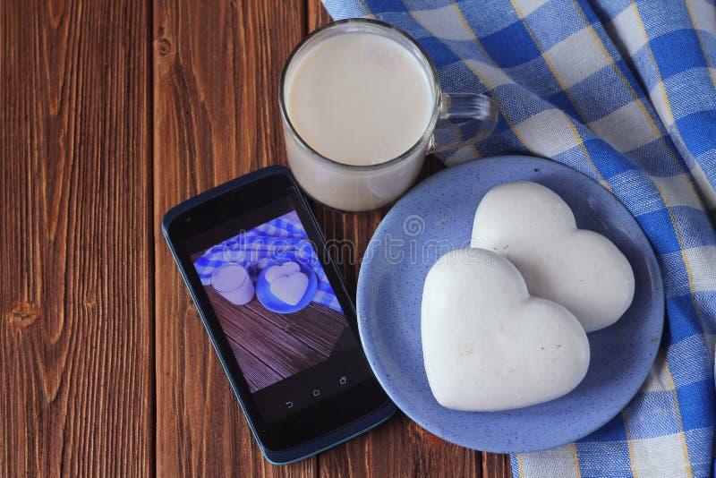 biscuits de gingembre sous forme de coeur sur une soucoupe, une tasse de chocolat chaud et le smarfon sur une table en bois photos stock