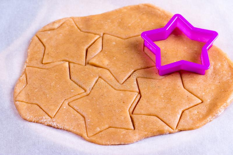 Biscuits de pain d'épice dans la fabrication sur les coupeurs crus de forme d'étoile de la pâte de pâtisserie en bois de planche  images libres de droits
