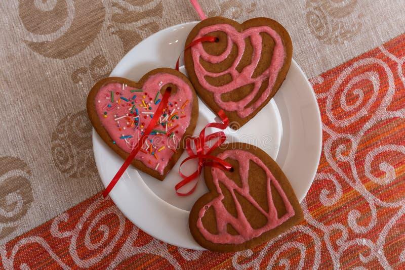 Biscuits de pain d'épice de chocolat en forme de coeur avec le glaçage rouge et rose du plat blanc images stock