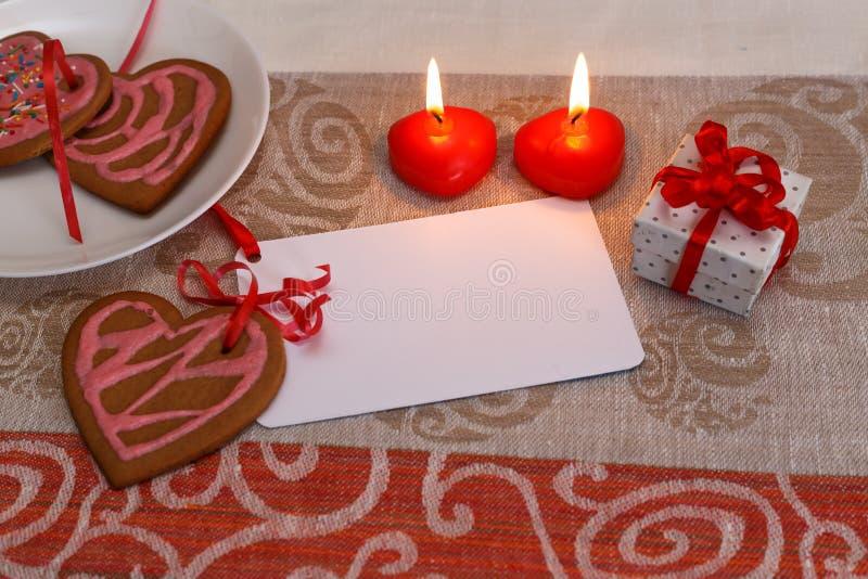 Biscuits de pain d'épice de chocolat en forme de coeur avec le glaçage rouge et rose et le ruban rouge après sur le tissu coloré photographie stock libre de droits