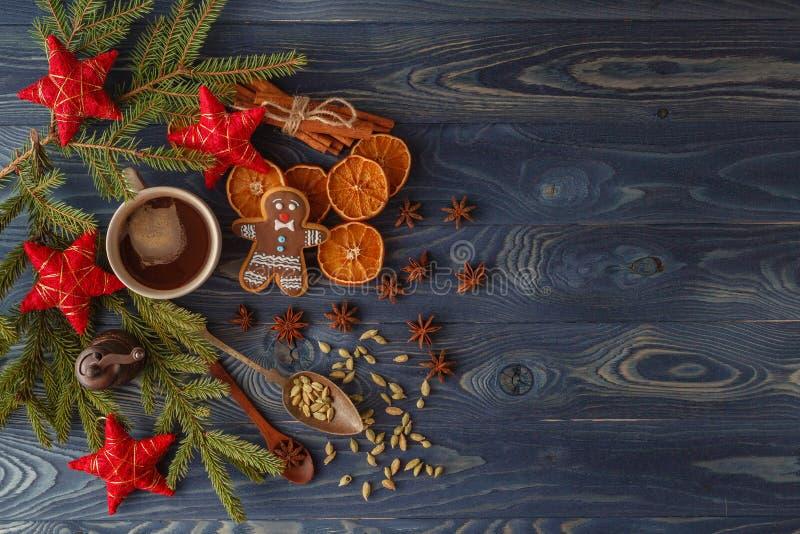 Biscuits de pain d'épice de Noël avec le glaçage, tasse de thé, sapin b photos stock