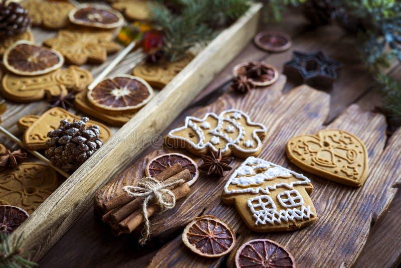 Biscuits de pain d'épice peints à la main et petit décor de Noël sur fond de bois ancien photos stock