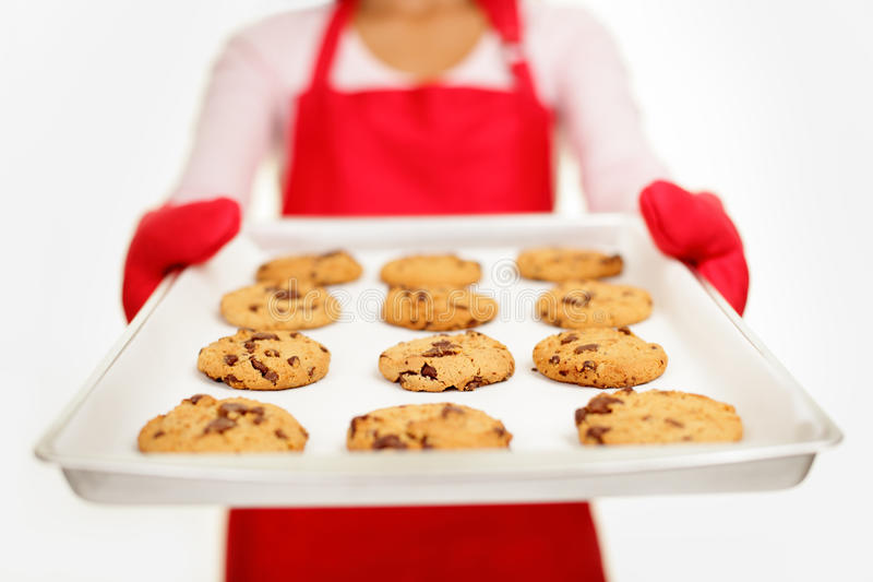 Biscuits de puce de chocolat - femme de traitement au four photographie stock libre de droits