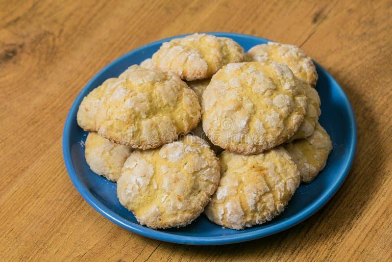 Biscuits de sucre faits maison de citron empilés sur la soucoupe bleue au fond en bois photographie stock libre de droits