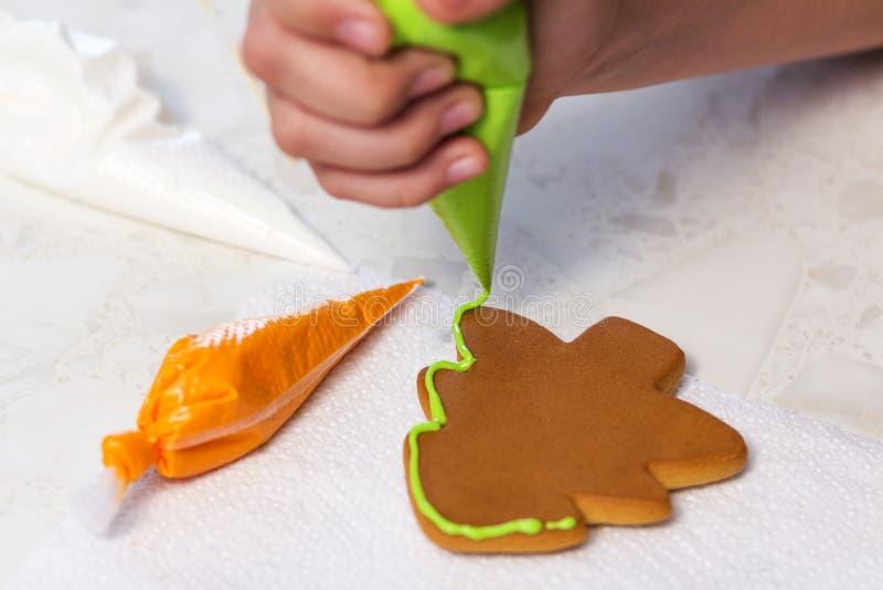Biscuits de vacances de cuisson L'enfant décore le pain d'épice fait maison sous forme d'arbre de Noël avec le lustre vert image stock