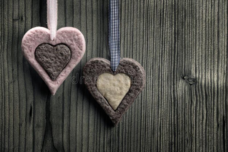Biscuits en forme de coeur avec deux couleurs - fond en bois photographie stock libre de droits