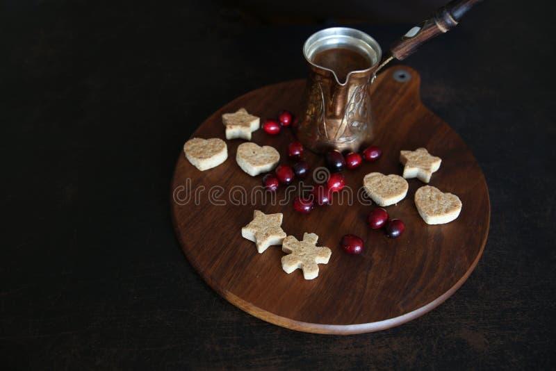Biscuits en forme de coeur avec du café et les baies rouges sur un fond en bois images libres de droits