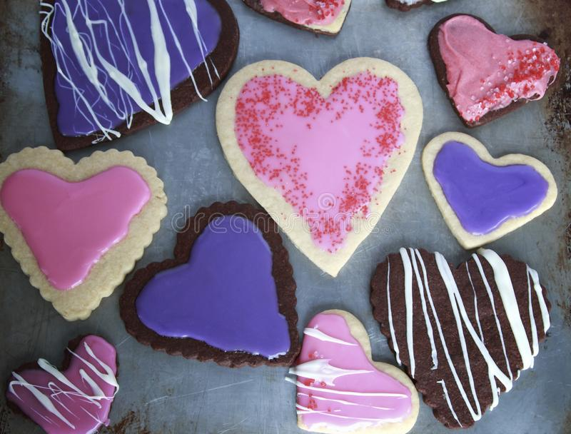 Biscuits en forme de coeur de vanille et de chocolat avec le rose et glaçage pourpre pour le jour de valentines sur la plaque à g photographie stock