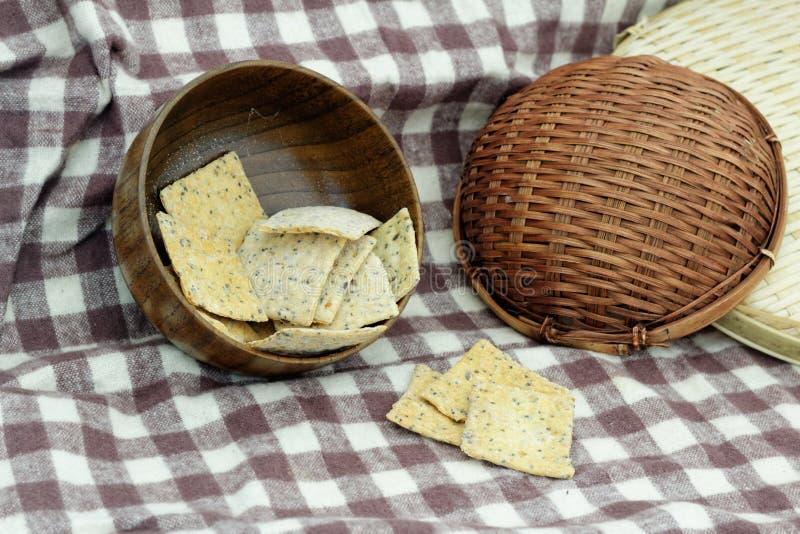 Biscuits entiers de grain/pain croustillant dans la cuvette en bois sur la table dans la cuisine photographie stock