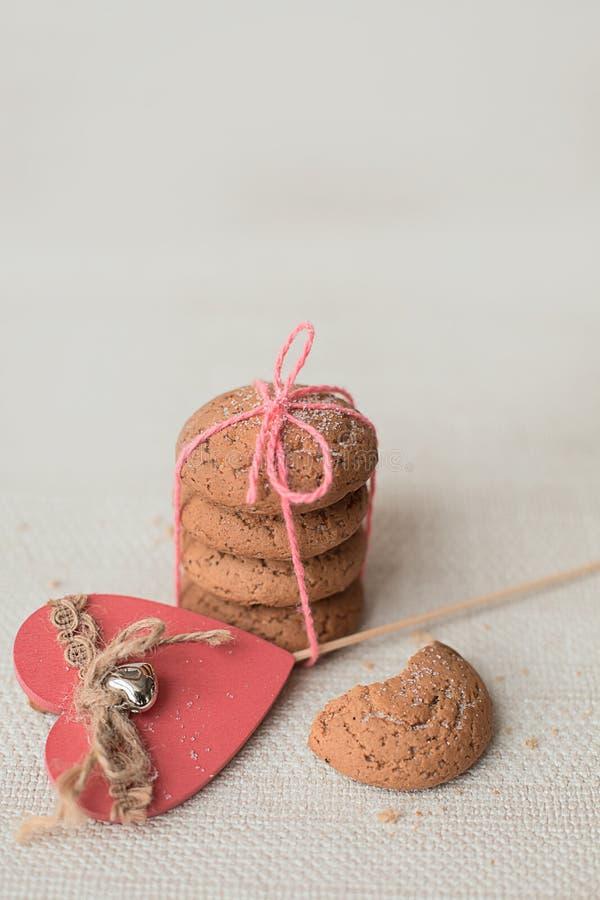 Biscuits et coeur rose sur un fond clair image stock