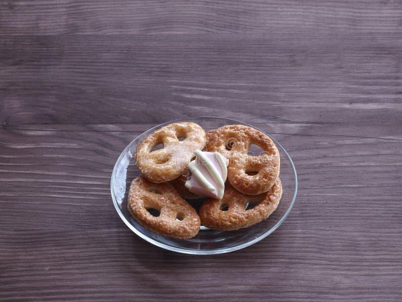Biscuits et guimauves faits maison d'une glace transparente sur une table en bois photo stock