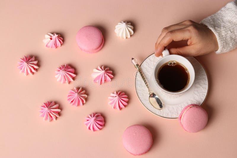 Biscuits et macarons de meringue sur un fond rose, la tasse de café et les mains des femmes images libres de droits