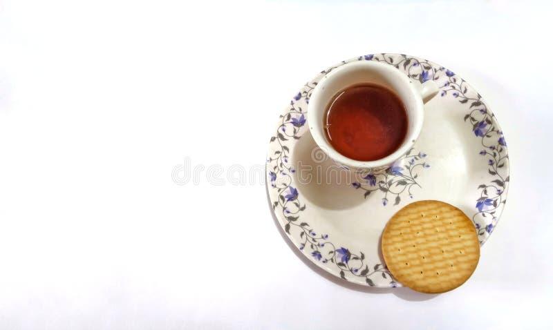 Biscuits et une tasse de th? rouge du plat d?coratif d'isolement sur le fond blanc images stock