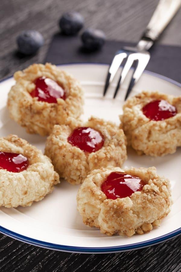 Biscuits faits à partir de la tarte sablée de noisette avec l'intérieur de confiture de fraise sur un plat blanc avec des myrtill photographie stock libre de droits