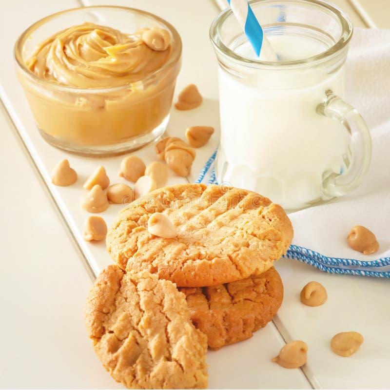 Biscuits faits maison délicieux de beurre d'arachide avec la tasse de lait Fond en bois blanc Image carrée Photo modifiée la tona image libre de droits