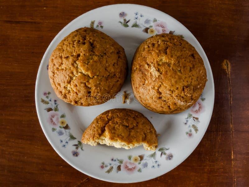 Biscuits faits maison dans un plat blanc sur une table foncée Un biscuit a fendu dans la moitié photo stock