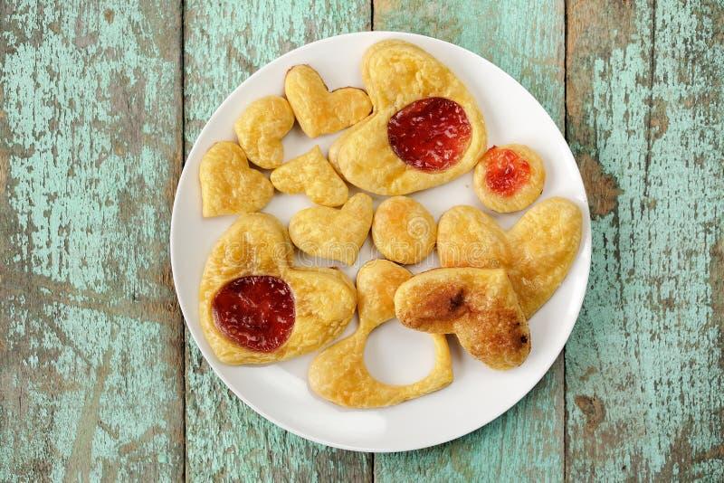 Biscuits faits maison de coeurs de souffle décorés de la confiture du plat blanc f image libre de droits