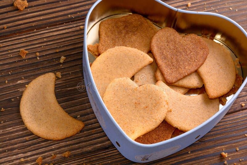 Biscuits faits maison de gingembre dans la boîte en forme de coeur sur le fond en bois photos stock