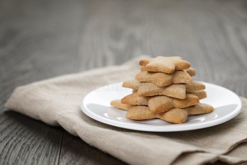 Biscuits faits maison de gingembre de forme d'étoile sur la table en bois images stock