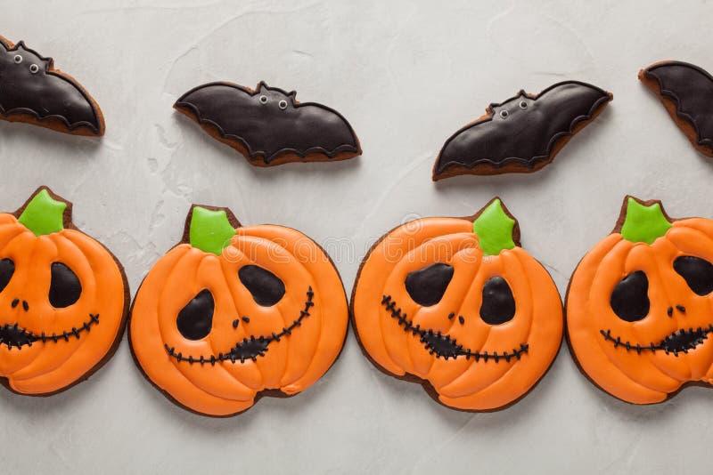 Biscuits faits maison de gingembre sous forme de potirons et battes Halloween Sur le fond concret plus clair Vue supérieure image stock