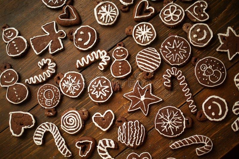 Biscuits faits maison traditionnels de gingembre et de chocolat de Noël décorés de la peinture de sucre blanc photos stock