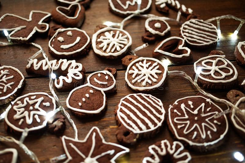 Biscuits faits maison traditionnels de gingembre et de chocolat de Noël décorés de la peinture de sucre blanc photos libres de droits
