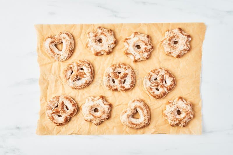 Biscuits fraîchement cuits au four de pain d'épice de Noël avec le glaçage sur le parchemin ou le papier de cuisson images libres de droits