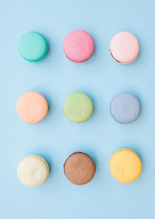Biscuits français colorés doux de macaron sur le fond bleu en pastel photo libre de droits