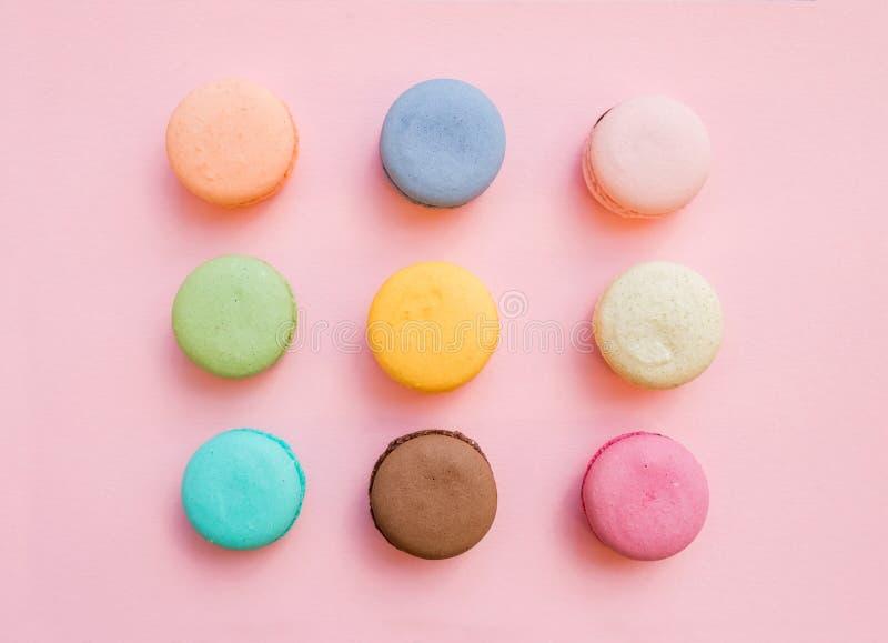 Biscuits français colorés doux de macaron sur le fond de rose en pastel images stock