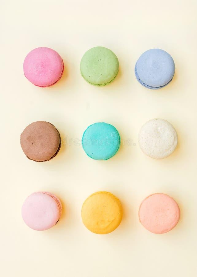 Biscuits français colorés doux de macaron sur le fond jaune en pastel photographie stock