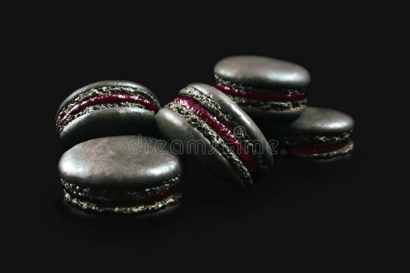 Biscuits français noirs de macaron avec le remplissage rouge foncé d'isolement sur le fond noir photos stock