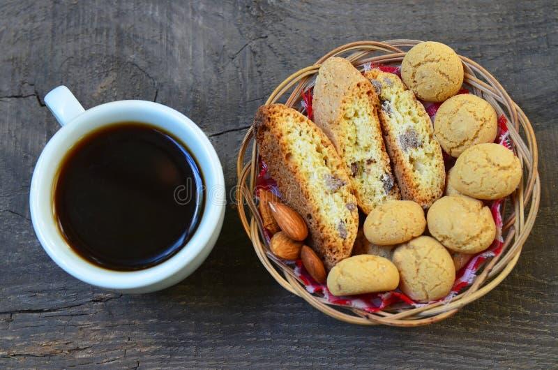 Biscuits italiens traditionnels de cantuccini et d'amaretti avec l'amande et la tasse de café sur le vieux fond en bois photos libres de droits