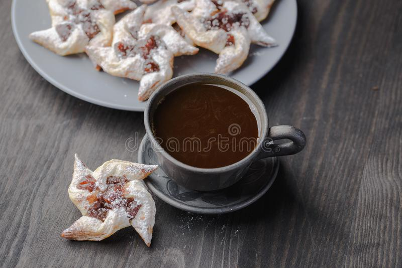 Biscuits with jam. Cup of coffee and a bun in the form of a rose,homemade buns with jam,homemade baking,puff pastries with a cup of coffee stock photo
