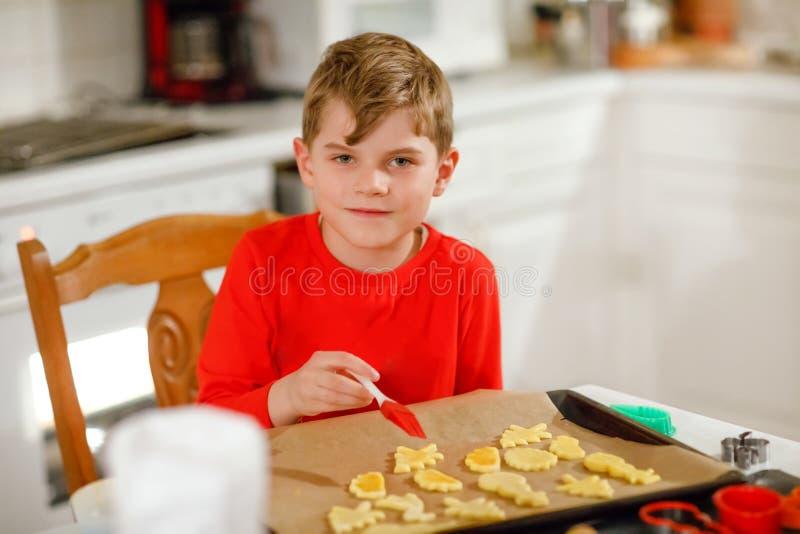 Biscuits mignons de Noël de pain d'épice de cuisson de petit garçon à la maison Enfant blond adorable ayant l'amusement dans la c photos libres de droits