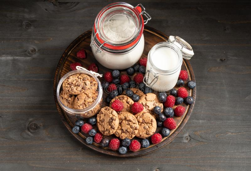 Biscuits, raspberries, blueberries, milk, flours jars over rounded wooden platter. stock images