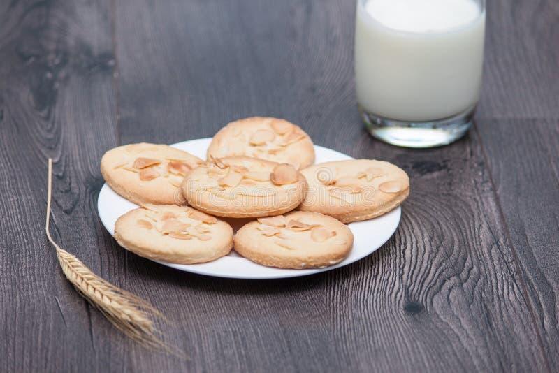 Biscuits savoureux avec l'amande et le blé du plat blanc sur le fond en bois Un verre de lait ou de yaourt avec des biscuits image stock