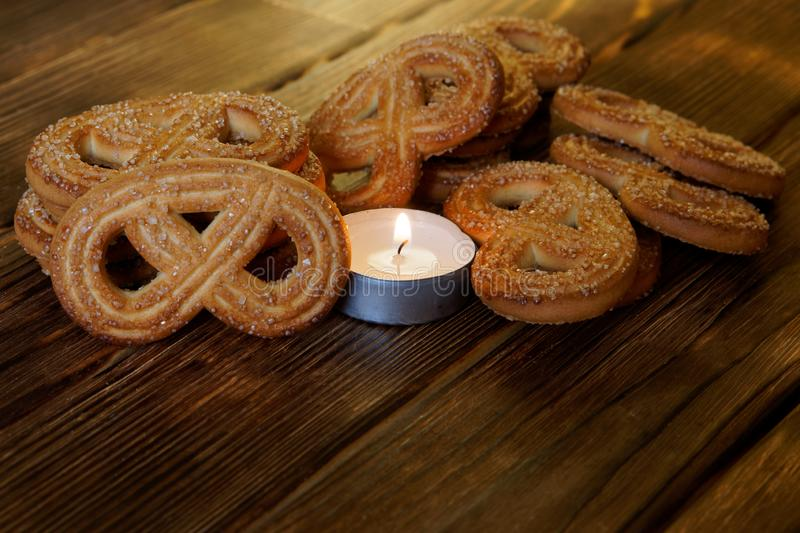 Biscuits with sugar lies next to a burning candle on a wooden surface. Closeup. Daylight royalty free stock images