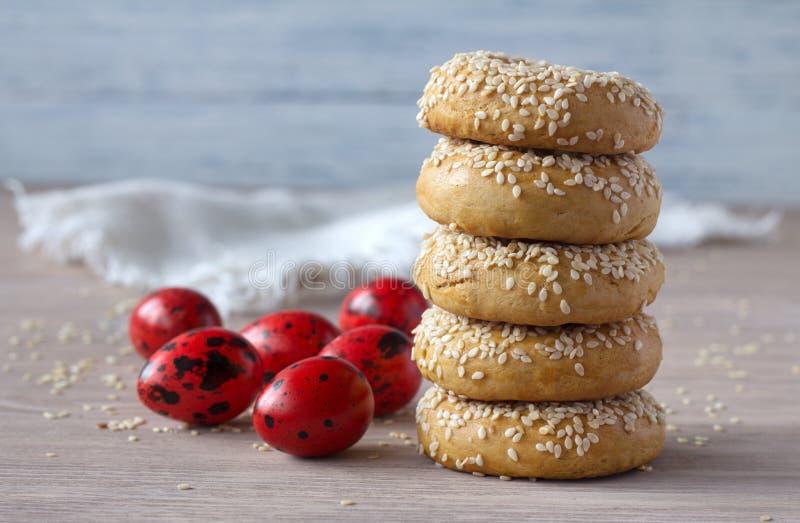 Biscuits traditionnels de Pâques de Grec avec les graines de sésame et les oeufs colorés photographie stock