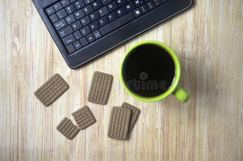 Biscuits at the wooden table with laptop and glass of coffee. Drink, green, technology stock photography