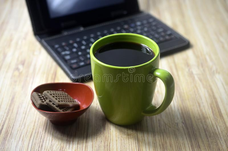 Biscuits at the wooden table with laptop and glass of coffee. Drink, green, technology, food royalty free stock images