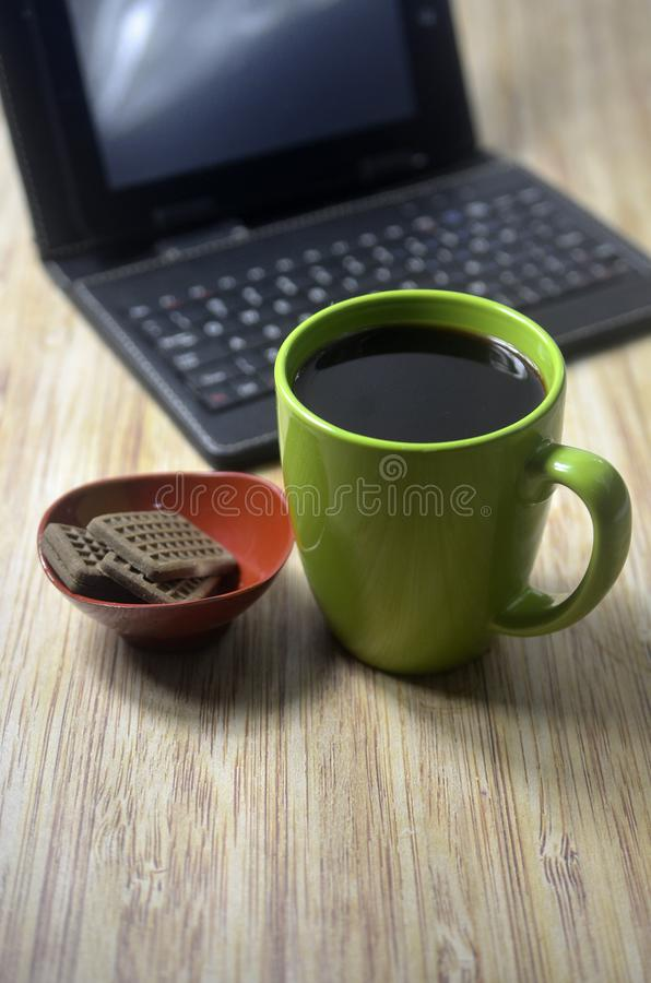 Biscuits at the wooden table with laptop and glass of coffee. Drink, green, technology, food stock images