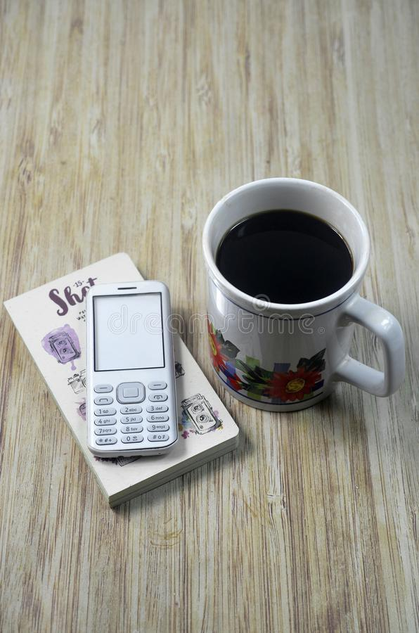 Biscuits at the wooden table with smartphone and glass of coffee. Biscuits at the wooden table with laptop and glass of coffee. Biscuits at the wooden table with stock photo