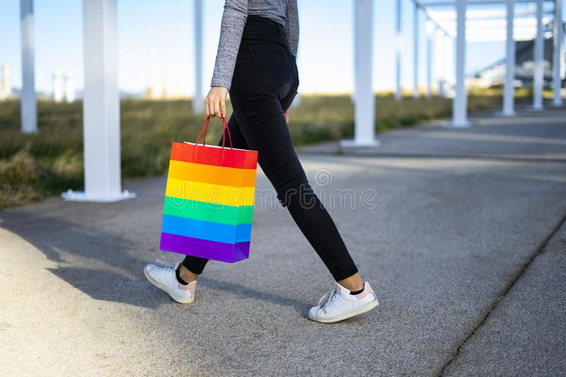 Bisexual woman carrying a bag with the Pride flag. On the city stock photo