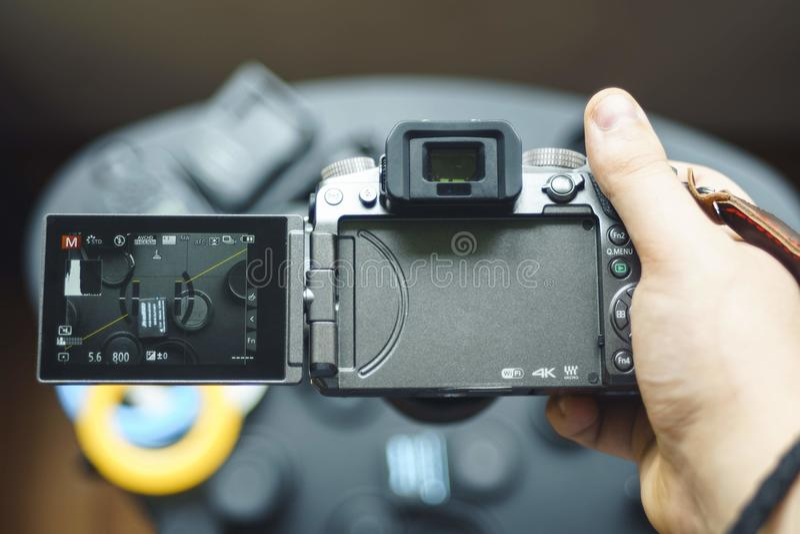 Camera Lumix G7. BISHEK, KYRGYZ REPUBLIC - APRIL 24,2018: Photo of PANASONIC LUMIX G7 mirrorless camera with digital display from behind. Man is holding the stock photography