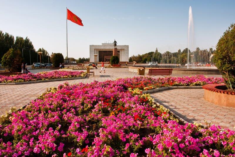 BISHKEK KIRGIZISTAN: Folket har att vila nära springbrunnarna & blomsterrabatterna på den huvudsakliga fyrkanten för staden fotografering för bildbyråer