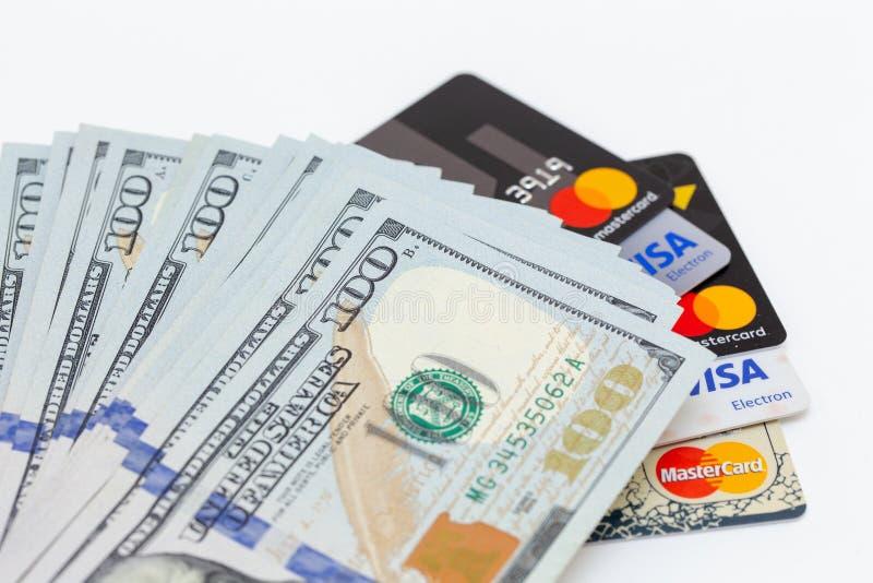 Bishkek, Kirguistán - 17 de febrero de 2019: cientos billetes de dólar y tarjetas de crédito visa y Master Card en el fondo blanc imagen de archivo