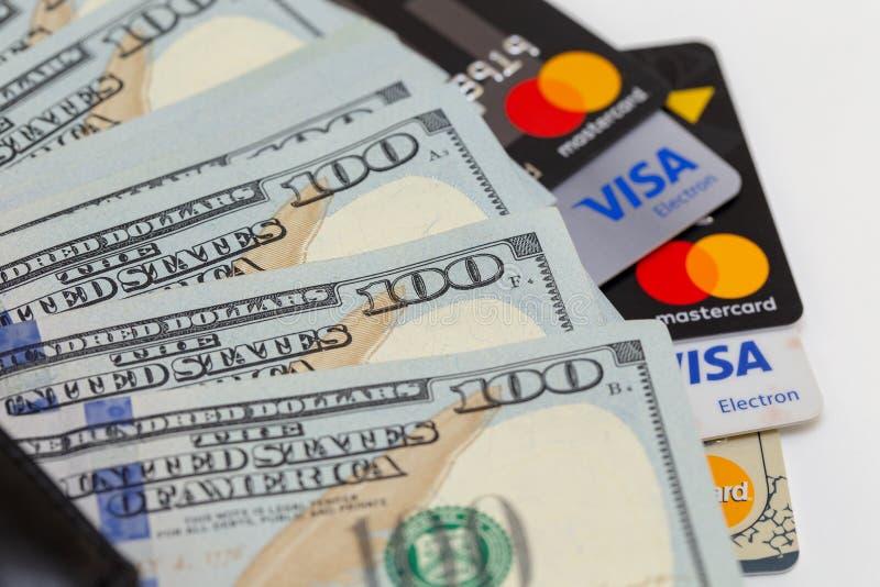 Bishkek, Quirguizistão - 17 de fevereiro de 2019: Carteira preta, cem notas de dólar e vistos dos cartões de crédito e cartão mes fotos de stock